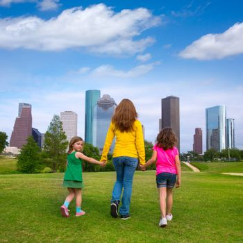 Mother and daughters walking holding hands on modern city skyline over park green lawn