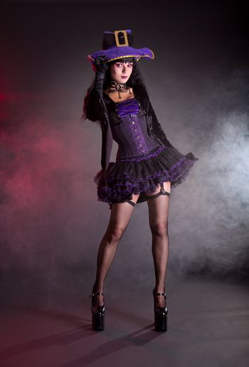 Sexy witch in purple and black gothic Halloween costume