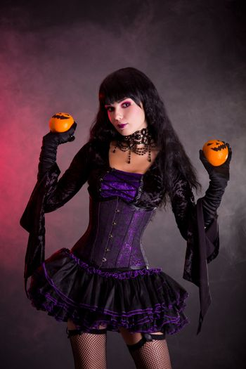 Attractive witch in purple gothic Halloween costume