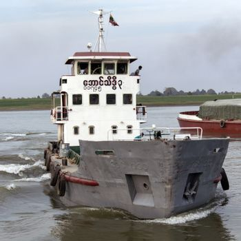 River traffic on the Irrawaddy River (Ayeyarwaddy River) in Myanmar (Burma).  It is the country's largest river and most important commercial waterway. Originating from the confluence of the N'mai and Mali rivers, it flows relatively straight North-South before emptying through the Irrawaddy Delta into the Andaman Sea.