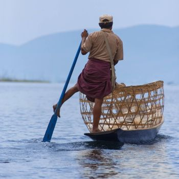 A leg rowing fishermen on Inle Lake in Shan State in Myanmar (Burma).This unique style of rowing evolved because the shallow lake bottom is covered by reeds and plants making it difficult to see the fish while sitting. Standing gives a better view.