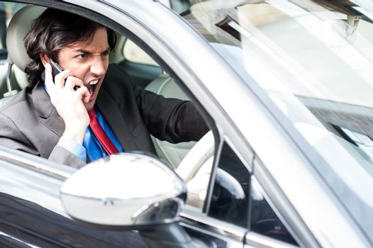 Angry businessman shouting while driving