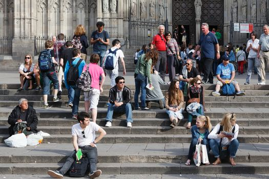 BARCELONA, SPAIN - APR 16, 2013 Tourists sit on the stairs of  Barcelona Cathedral on April 16, 2013 in Barcelona, Spain. The Cathedral of the Holy Cross and Saint Eulalia, (Barcelona Cathedral), is the Gothic cathedral and seat of the Archbishop of Barcelona