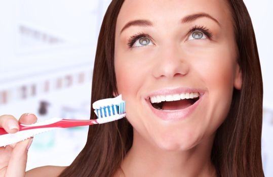 Closeup portrait of beautiful woman clean teeth in the bathroom at home, looking up, perfect smile, dental treatment, refreshment concept