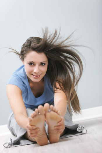 Portrait of a smiling girl doing stretching exercise on floor
