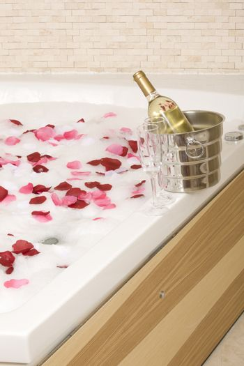 A relaxing bath with rose petals ,wine and glassess