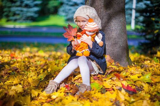 Pretty Fashion girl sits under a maple tree with doll and red leaf on sunny autumn day