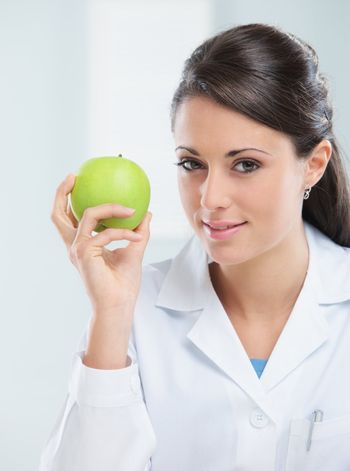 Nutritionist female Doctor holding a green apple