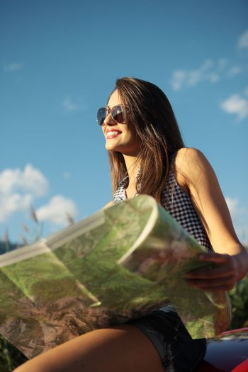 Young beautiful woman wearing sunglasses holding a roadmap