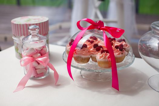 Jug of parisian colorful macarons and tasty cakes on the wedding table