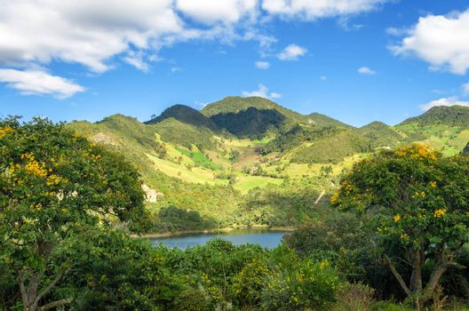 Lush green hills and a lake in Neusa, Colombia