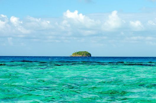 Small green island on the horizon of the Caribbean Sea near San Andres y Providencia, Colombia