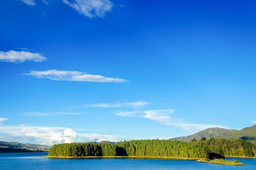 Beautiful blue lake with a wooded island and green hills in Neusa, Colombia