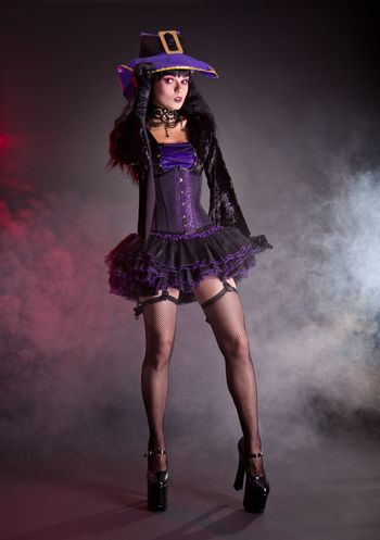 Pretty witch in purple and black gothic Halloween costume