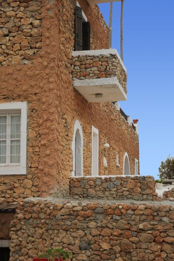 ancient Greek house with a stone staircase and balcony
