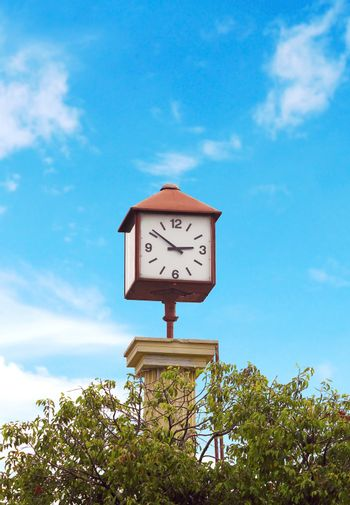 Clock tower in the park with blue sky background