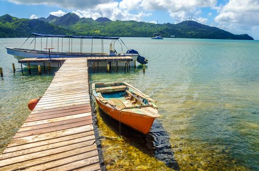 Orange boat and pier with view of San Andres y Providencia, Colombia in the background