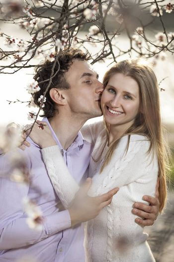 Young romantic couple hugging in the spring blossom