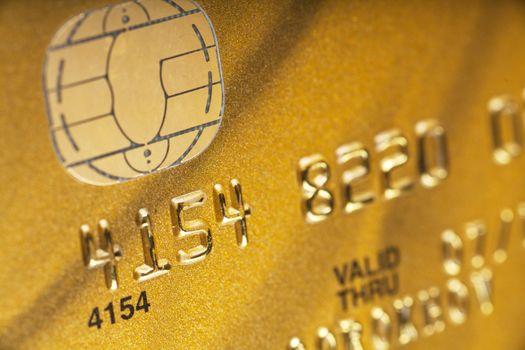 Macro view of golden credit card. Narrow focus.