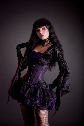 Romantic gothic girl in purple and black gothic Halloween outfit