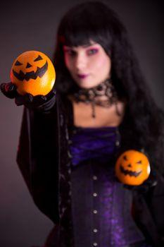 Pretty witch holding Jack o lantern oranges