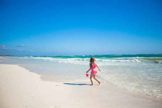 Adorable little girl in swimsuit having fun at tropical carribean beach
