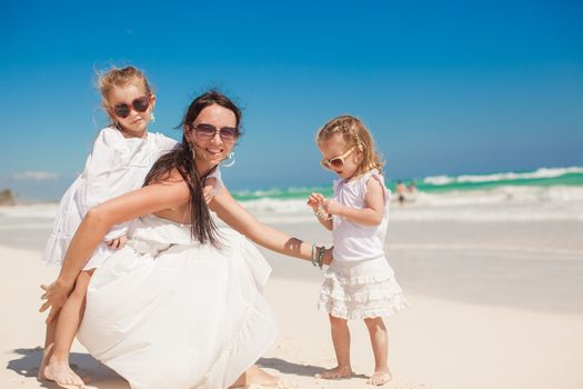 Two wonderful girls having fun with their charming young mother on the white carribean beach,
