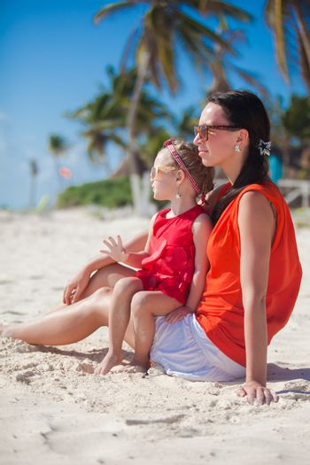 Little girl  with her young mom relaxing on carribean beach