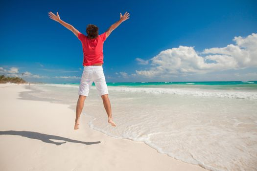 Young man jumping and raising his arms up on carribean beach