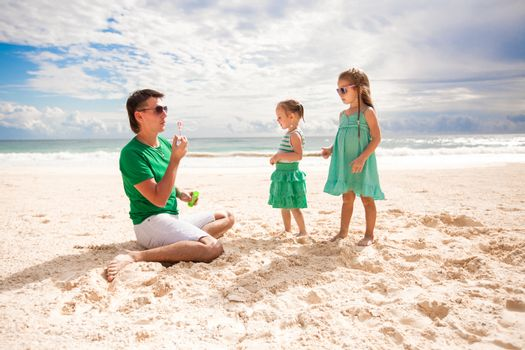 Young father and his adorable little daughters have fun at carribean beach