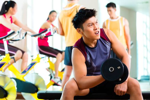 Chinese Asian group of men and woman doing sport exercise or training in fitness gym with barbell weights for more power
