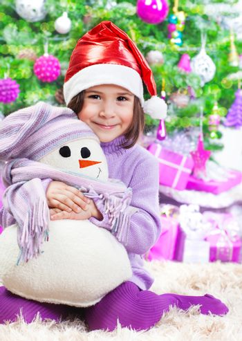 Cute little girl sitting on the floor under big decorated Christmas tree, wearing red Santa hat, holding in hands white snowman soft toy, New Year holidays