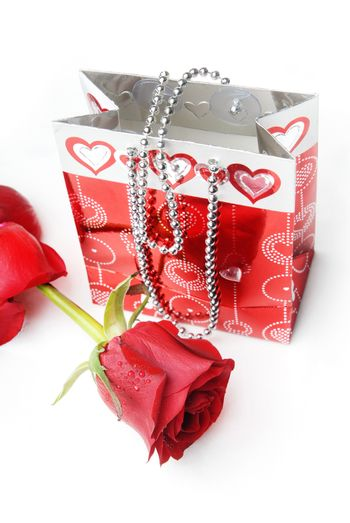 Red rose and package with hearts as a gift for Valentine day