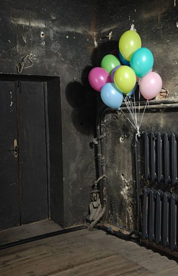 Celebrating colorful balloons in trashy dark interrior for Halloween
