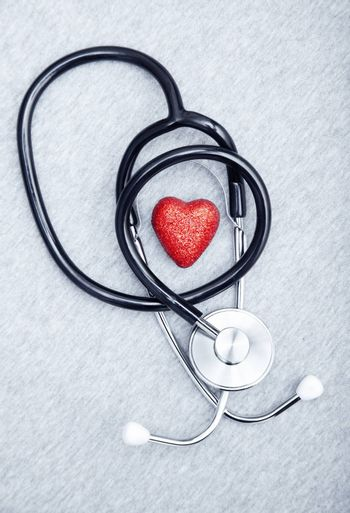 Medical stethoscope and heart on a textured background
