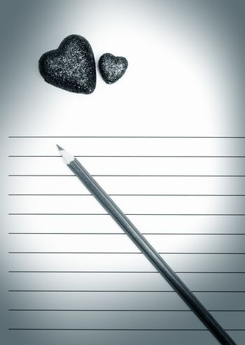 Pencil and two hearts on a blank love letter