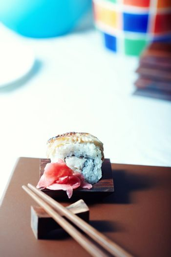Close-up vertical photo of the rolled sushi with rice and cucumber on the table. Shallow depth of field for natural view