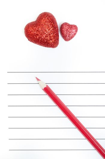 Red pencil and two hearts on a blank love letter