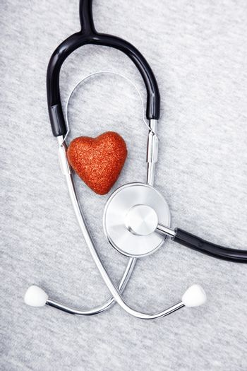 Medical stethoscope and heart on a blue textured background