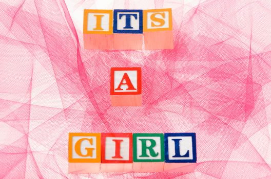 Letter blocks spelling its a girl shot on a pink background