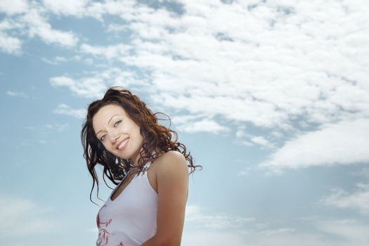 Smiling successful lady outdoors and cloudy sky on the background