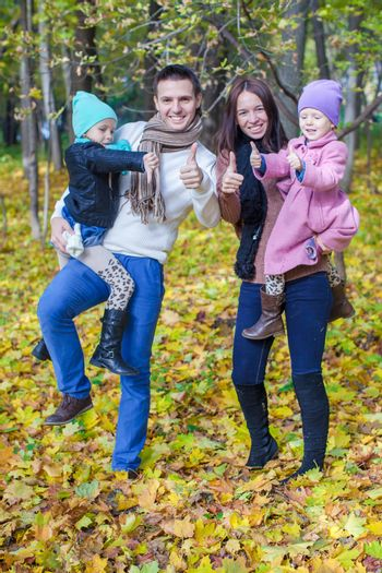 Young parents with two little daughters in autumn yellow park