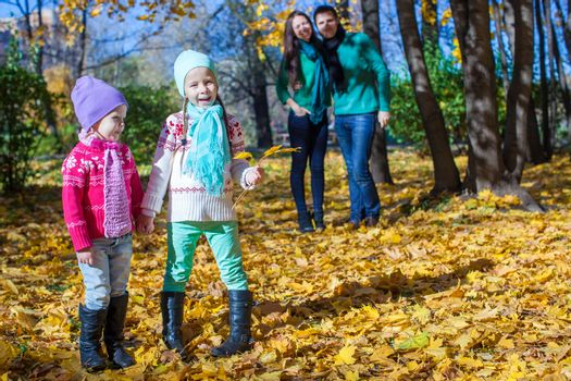 Two little girls on background of his parents at the park in autumn