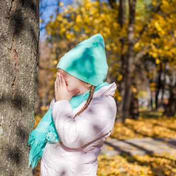 Little girl playing hide and seek in the autumn forest