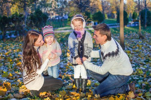 Young beautiful family of four enjoyed relaxing in autumn park