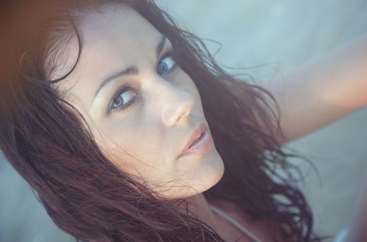 Pensive woman with wet hairs in the water. Natural light and colors