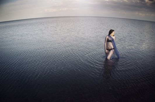 Woman in the sea before the storm. Horizontal photo. Artistic horizon distortion added due to the wide angle lens