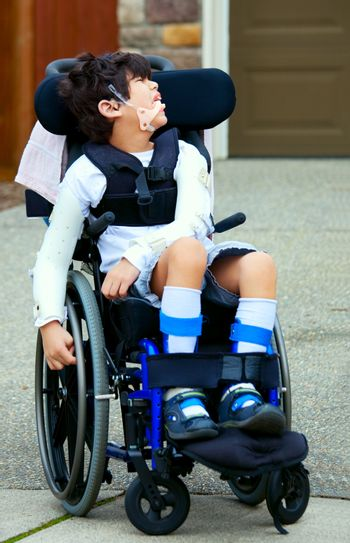 Seven year old biracial disabled boy in wheelchair