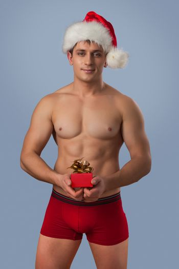 a muscular naked man in santa cup