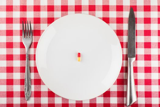 Closeup view of single capsule on a white plate with fork and knife